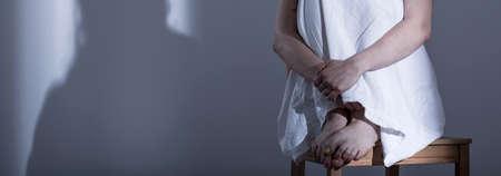 violencia sexual: Panorama de violaci�n asustada v�ctima sentada acurrucada en la silla