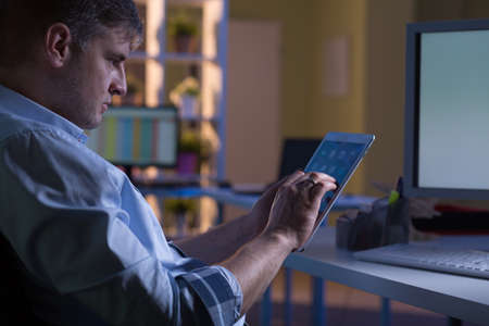 earnest: Experienced man is using modern technology in the work Stock Photo
