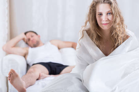 staying: Young couple staying in bed after argument