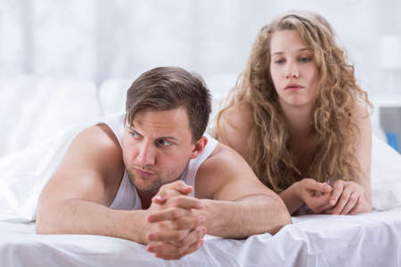 argument from love: Couple is lying in bed and sad after having argument Stock Photo
