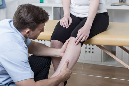 physical injury: Young physiotherapist diagnosing patient with painful knee Stock Photo