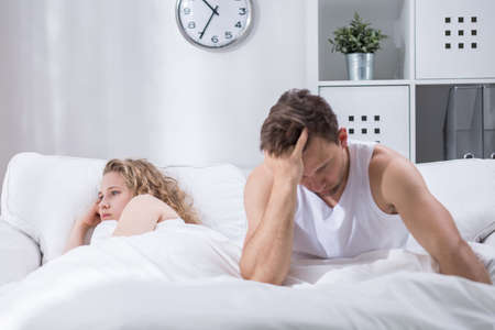 frustrated man: Couple is lying in bed upset after argument