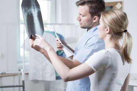 dislocation: Fisioterapeuta joven está mirando la radiografía de la columna vertebral