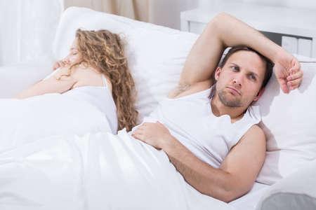 男はガール フレンドとの考え方とベッドに横たわっています。