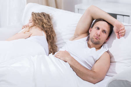 pareja durmiendo: Man is lying in bed with girlfriend and thinking Foto de archivo