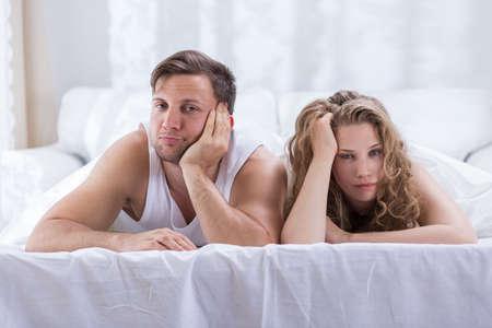 mujer en la cama: Pareja en la cama no está hablando tras una discusión
