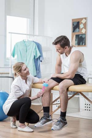 luxacion: Joven fisioterapeuta paciente ayudando con cinta Kinesio