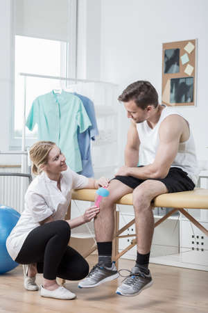 wrest: Young physiotherapist helping patient with kinesio tape Stock Photo