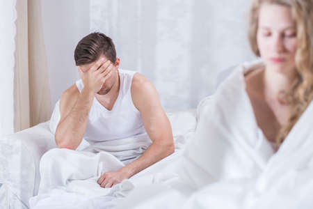 Man and woman sitting unhappy in bed