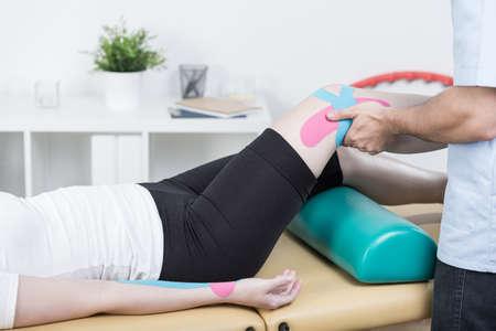 de rodillas: fisioterapeuta joven se está grabando brazo y la pierna