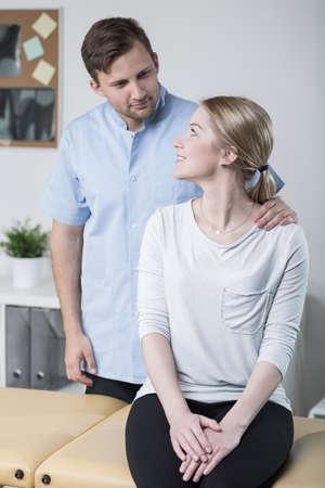 dislocation: fisioterapeuta joven está entrevistando paciente lesionado femenina