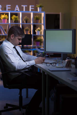 after hours: Young man is working in the office after hours