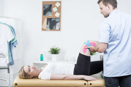 wrest: Young physiotherapist using physio tape for knee Stock Photo