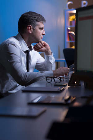 after hours: Experienced manager is working after hours in the office Stock Photo