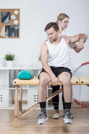 luxacion: Terapeuta físico está examinando hombre sobreentrenamiento joven