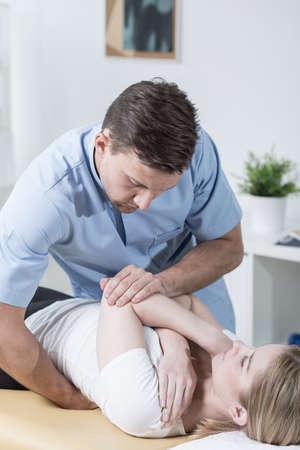 luxacion: Paciente joven formación fisioterapeuta con el hombro lesionado