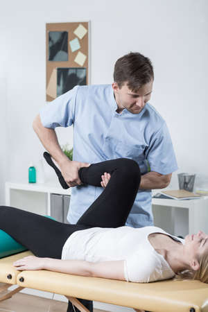 wrest: Young physiotherapist is doing exercises with patient
