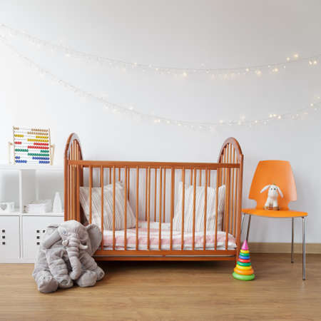 toys: Image of child room with wooden crib and pink carpet Stock Photo