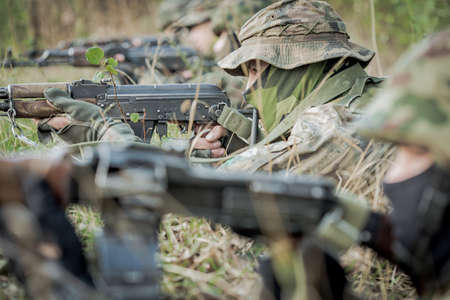 proving: Soldiers lying on ground and holding gun