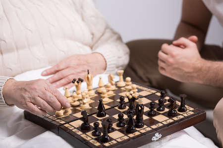 afflictions: Photo of carer playing chess with rest home resident