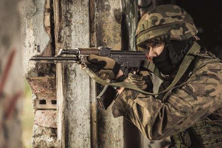 khakis: Horizontal photo of soldier using automatic weapon