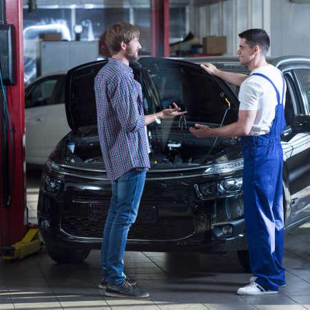 automotive technician: Young automotive technician talking with male client