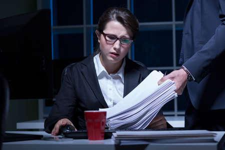 眠そうな女性のオフィスで残業 写真素材