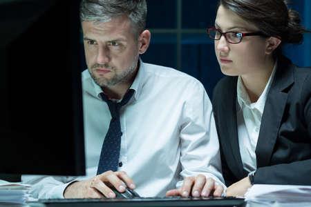 empleados trabajando: Dos empleados que trabajan en el ordenador después de hora