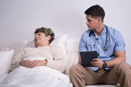 geriatric: Image of doctor and suffering geriatric ward patient Stock Photo