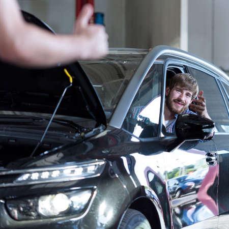 auto repair: Picture of happy driver in auto repair shop