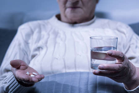 afflictions: Image of senior woman holding pills and glass of water Stock Photo