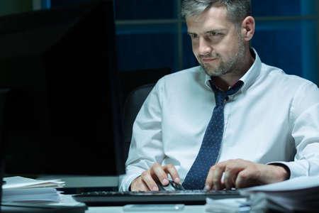 trabajando duro: Jefe guapo trabajando duro en la noche en la oficina