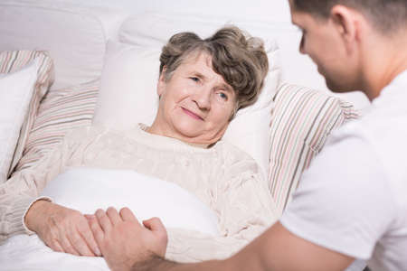 geriatric care: Photo of geriatric ward patient with helpful grandson Stock Photo