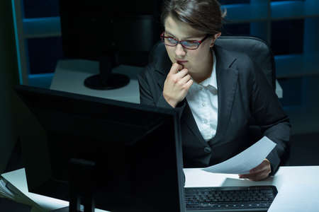 night shift: Young busy woman in office having night shift at work