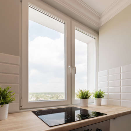 house windows: Close-up on a bright kitchens window overlooking neighborhood Stock Photo