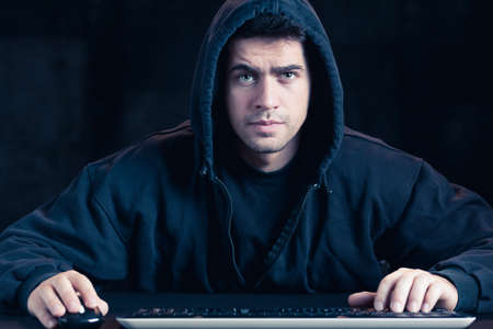 cyber warfare: Photo of young cyber warior in black hoody