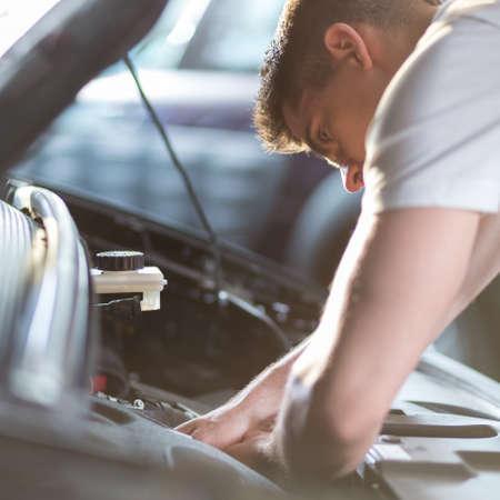 mecanico automotriz: Automóvil mecánico de reparación de un coche en la estación de servicio