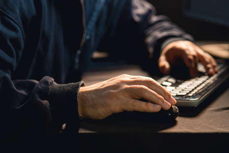 cyber warfare: Photo of male hacker typing on pc keyboard
