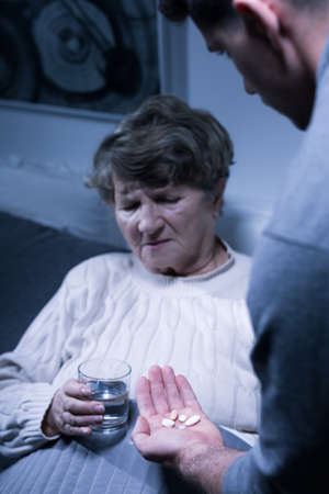 carer: Image of male carer and elderly woman taking medicines
