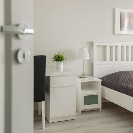 ajar: Vertical view of open door to cozy bedroom Stock Photo