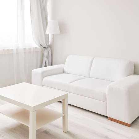 Picture of small table and sofa in simply furnished lounge