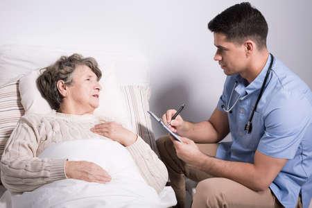 afflictions: Image of handsome doctor examining senior alzheimer patient