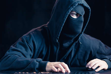 online security: Photo of dangerous cyber terrorist in black mask Stock Photo