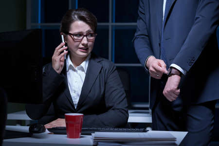 after hours: Worried young woman working in office after hours
