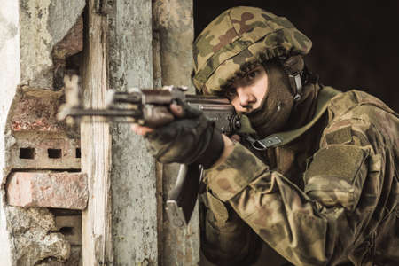 khakis: Military soldier is firing weapon during training