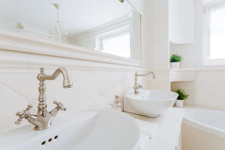 washbasins: Close-up on chrome taps and accents in creamy bathroom Stock Photo