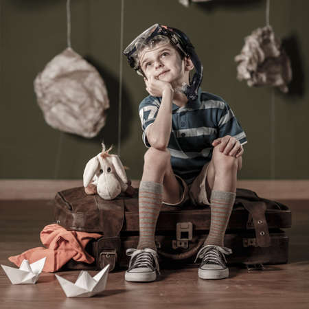 daydreamer: Little daydreamer sitting on suitcase and dreaming about diving