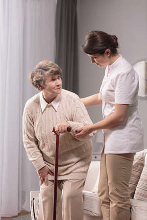 assisting: Photo of senior with walking problem and her caregiver Stock Photo