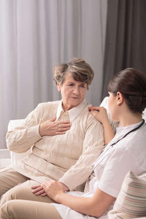 afflictions: Photo of ill senior with painful afflictions and carer Stock Photo