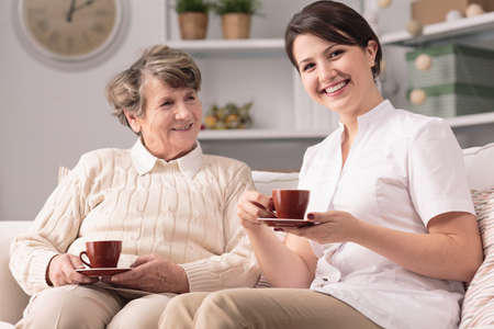 home health care: Image of private caregiver and senior female smiling